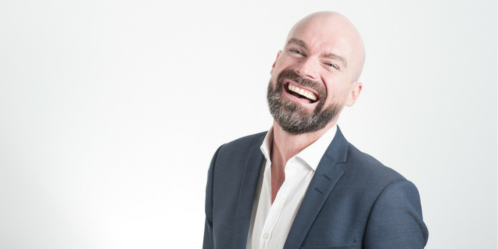 shaved head man laughing in suit