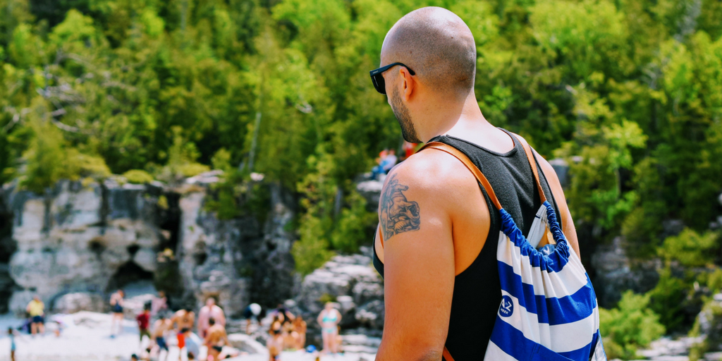 Man that is balding looks to the beach while wearing his backpack