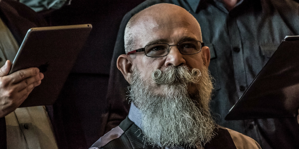 Old balding man with glasses and huge beards