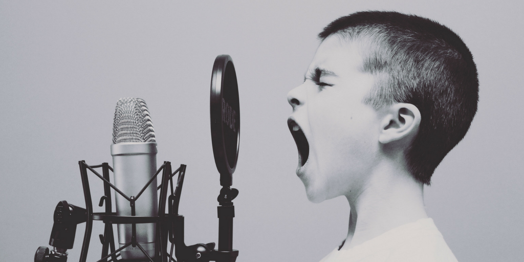 kid is screaming in front of a radio microphone because he is balding